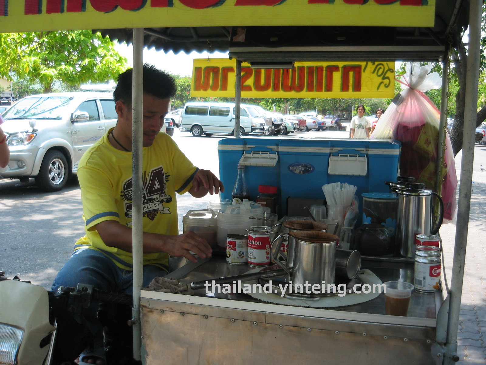 Buying coffee from roadside peddler in Thailand
